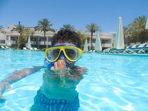 Boy swimming at pool with mask. Happy little boy swimming at pool with diving mask stock photography