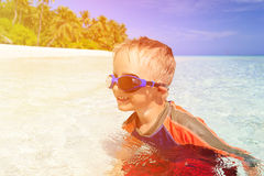 Happy little boy swimming on tropical beach Royalty Free Stock Photo