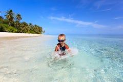 Happy little boy swimming on tropical beach Stock Photos