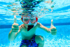 Happy little boy swimming underwater with thumbs up Royalty Free Stock Images