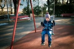 Happy little boy on swing in beautiful winter day have fun and makes faces. One person. Swinging on the swing in playground area stock photography