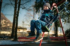 Happy little boy on swing in beautiful winter day. Have fun and makes faces. One person. Swinging on the swing in playground area Royalty Free Stock Photos