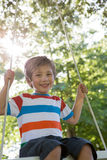 Happy little boy on a swing in the park Royalty Free Stock Images