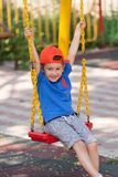 Happy little boy swinging on chain swing. Outdoor playground. With hat Stock Photo