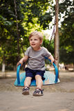 Happy little boy swinging on a swing Stock Images