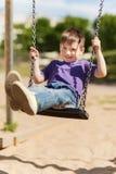 Happy little boy swinging on swing at playground Stock Image