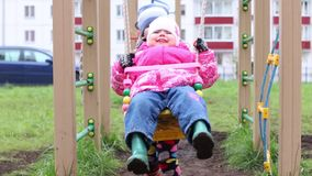 Happy little boy swings his little sister on playground stock video footage