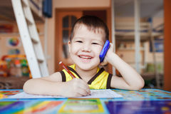 Happy little boy talking on smartphone at home stock image