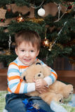 Happy little boy with a teddy bear in a Christmas tree (3 years Stock Photos