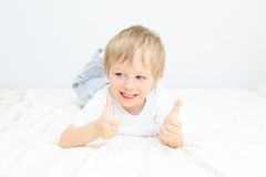 Happy little boy with thumbs up on white Royalty Free Stock Images