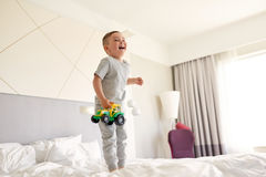 Happy little boy with toy car on home or hotel bed Royalty Free Stock Photos