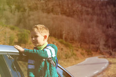 Happy little boy travel by car in autumn Royalty Free Stock Photos