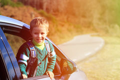 Happy little boy travel by car in autumn nature Royalty Free Stock Image
