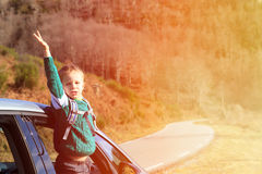Happy little boy travel by car in autumn nature Stock Images