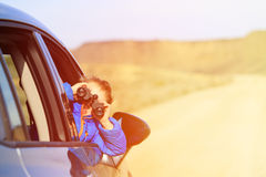 Happy little boy travel by car in mountains Stock Image