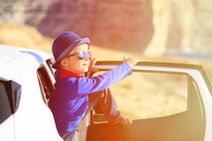 Happy little boy travel by car in mountains Stock Photography