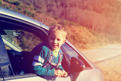 Happy little boy travel by car in nature Stock Images