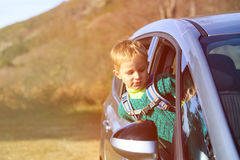 Happy little boy travel by car in nature Royalty Free Stock Image