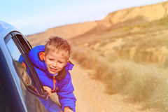 Happy little boy travel by car on road to mountains Royalty Free Stock Photo