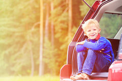 Happy little boy travel by car in summer nature Royalty Free Stock Image