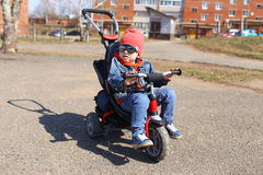 Happy little boy on tricycle in springtime Stock Images