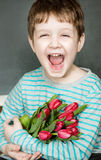 Happy little boy with tulips. Royalty Free Stock Photos
