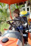 Happy little boy of two years having fun on tractor in summer Stock Photography