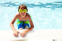 Happy little boy typing on laptop in swimming pool Royalty Free Stock Photos