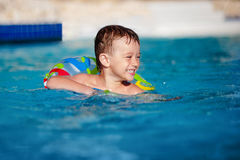 Happy little boy with variegated life ring has fun in the swimming pool.   into resort Stock Photography