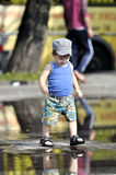 Happy little boy in vest and shorts walks on a puddle. Happy little boy in vest and shorts walks on puddle Royalty Free Stock Images