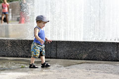 Happy little boy in vest and shorts walks on a puddle. Happy little boy in vest and shorts walks Royalty Free Stock Photo