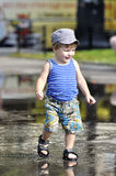 Happy little boy in vest and shorts walks on a puddle. Happy little boy in vest and shorts walks on puddle Stock Images