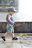 Happy little boy in vest and shorts walks on a puddle Royalty Free Stock Photography