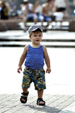 Happy little boy in vest and shorts walks on street Royalty Free Stock Images