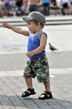 Happy little boy in vest and shorts walks on street Stock Photo
