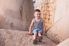 Happy little boy in vest sits on breakwater in port. Happy smiling little boy in sailor vest sitting on breakwater in port royalty free stock photography