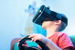 Happy little boy in virtual reality glasses playing video game Royalty Free Stock Photo