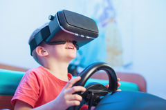 Happy little boy in virtual reality glasses playing video game Royalty Free Stock Images