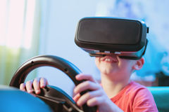 Happy little boy in virtual reality glasses playing video game Royalty Free Stock Photos