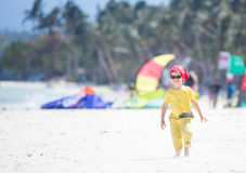 Happy little boy walking along a beach Stock Photo