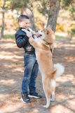 Happy little boy walking with dog in the park. Animal concept. Smiling happy little boy having fun with doggie in the park outdoors. Cute kid with puppy playing Stock Images