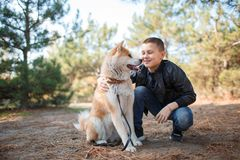 Happy little boy walking with dog in the park. Animal concept. Smiling happy little boy having fun with doggie in the park outdoors. Cute kid with puppy playing Stock Image