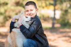 Happy little boy walking with dog in the park. Animal concept. Smiling happy little boy having fun with doggie in the park outdoors. Cute kid with puppy playing Royalty Free Stock Photo