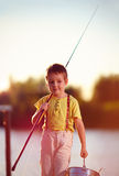 Happy little boy walking after successful fishing on the pond. At sunset Royalty Free Stock Images
