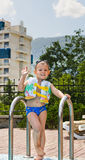 Happy little boy waving at the camera poolside. As he stands on the steps at the edge swimming pool ready to take dip Stock Photography