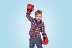 Happy little boy wearing boxing glovesa and celebrating success. With golden medal isolated over blue background Royalty Free Stock Photography