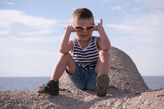 Happy little boy wearing sunglasses and striped vest and jean shorts near sea Royalty Free Stock Photos