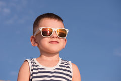 Happy little boy wearing white sunglasses on blue sky background Royalty Free Stock Photo