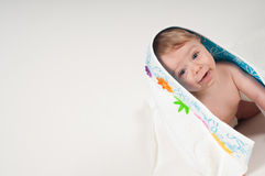 Little boy in white blanket with flowers Stock Photos