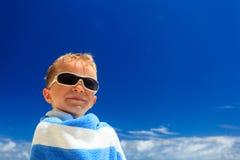 Happy little boy wrapped in beach towel on sky Stock Image
